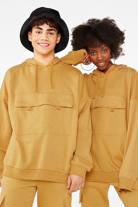 Two friends wearing matching golden tan oversized hoodie and cargo sweatpants.