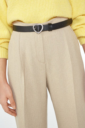 Girl wearing a yellow sweater, beige trousers and a black belt with a heart buckle.