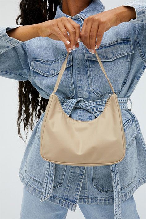 Girl wearing matching light denim jackets and jeans, holding a beige shoulder bag.