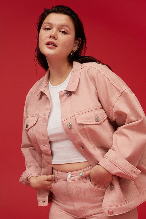 Girl wearing matching pink denim jacket and jeans and a white top.