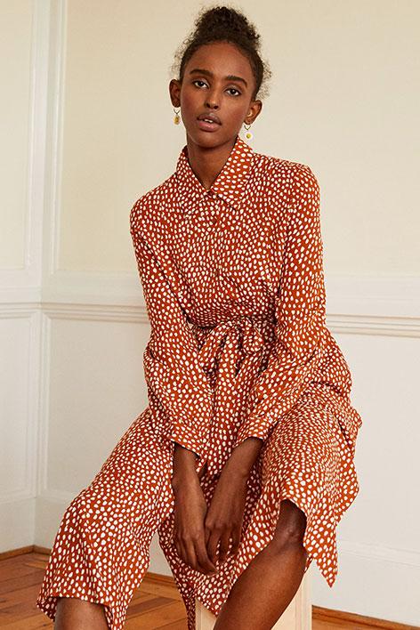 Girl wearing a rusty shirt dress with polka dots.